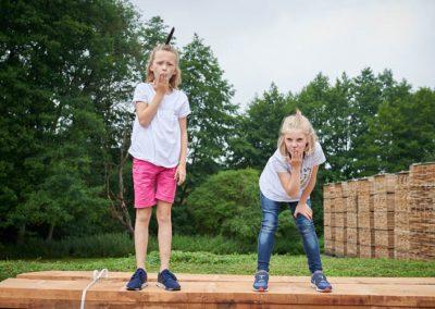 Zwei Mädchen auf einem Stapel Holzbretter machen Kuss-Hand