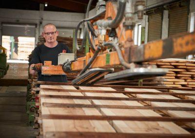 Mitarbeiter bearbeitet Holz mit einer Maschine